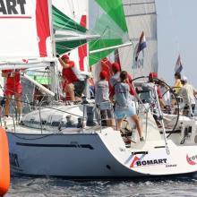 Posádky Bomart a POHL otáčí návětrnou bóji a vytahují spinakry.